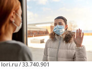woman in mask looking to friend through window. Стоковое фото, фотограф Syda Productions / Фотобанк Лори