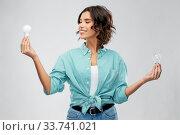 Купить «smiling woman comparing different light bulbs», фото № 33741021, снято 18 апреля 2020 г. (c) Syda Productions / Фотобанк Лори