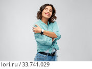 Купить «smiling woman with smart watch hugging herself», фото № 33741029, снято 18 апреля 2020 г. (c) Syda Productions / Фотобанк Лори