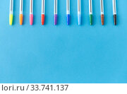 row of multicolored pens on blue background. Стоковое фото, фотограф Syda Productions / Фотобанк Лори