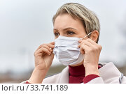 Купить «young woman wearing protective medical mask», фото № 33741189, снято 9 апреля 2020 г. (c) Syda Productions / Фотобанк Лори