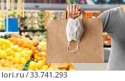 Купить «woman with shopping bag and mask at grocery», фото № 33741293, снято 3 апреля 2020 г. (c) Syda Productions / Фотобанк Лори
