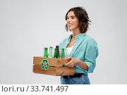Купить «smiling young woman sorting glass waste», фото № 33741497, снято 18 апреля 2020 г. (c) Syda Productions / Фотобанк Лори