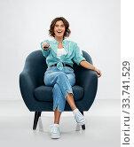 Купить «happy woman sitting in armchair with tv remote», фото № 33741529, снято 18 апреля 2020 г. (c) Syda Productions / Фотобанк Лори