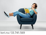 bored woman in armchair reading book and yawning. Стоковое фото, фотограф Syda Productions / Фотобанк Лори