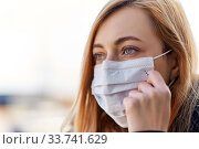 Купить «young woman wearing protective medical mask», фото № 33741629, снято 9 апреля 2020 г. (c) Syda Productions / Фотобанк Лори