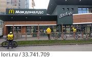 Курьеры Яндекс-Еды ожидают перед Макдональсом когда будут готовы заказы. Кафе закрыто, работает только доставка (2020 год). Редакционное фото, фотограф Ирина Терентьева / Фотобанк Лори