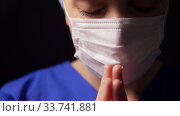 female doctor or nurse in face mask praying. Стоковое видео, видеограф Syda Productions / Фотобанк Лори
