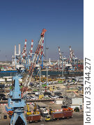 Купить «Four-link cargo loading crane on dock with parked motor vehicles ready for shipping plus container loading cranes in background, Ashdod Port, Israel.», фото № 33744277, снято 4 октября 2019 г. (c) age Fotostock / Фотобанк Лори