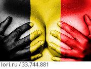 Купить «Sweaty upper part of female body, hands covering breasts, flag of Belgium», фото № 33744881, снято 5 июня 2020 г. (c) age Fotostock / Фотобанк Лори