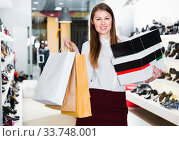 Portrait of young woman which is showing purchases in shoes store. Стоковое фото, фотограф Яков Филимонов / Фотобанк Лори