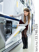 Modern female housewife buying dishwasher in domestic appliances section. Стоковое фото, фотограф Яков Филимонов / Фотобанк Лори