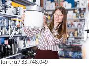 Glad woman choosing slow cooker in shop. Стоковое фото, фотограф Яков Филимонов / Фотобанк Лори