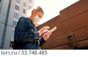Купить «Woman wearing glasses and protective medical mask and rubber gloves using smart phone at city. Health and safety, N1H1 corona virus, virus protection care and medical concept», видеоролик № 33748485, снято 14 мая 2020 г. (c) Ekaterina Demidova / Фотобанк Лори