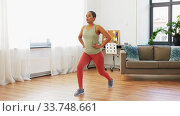 Купить «african woman doing lunge exercise at home», видеоролик № 33748661, снято 28 марта 2020 г. (c) Syda Productions / Фотобанк Лори