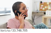 Купить «african woman calling on smartphone at home», видеоролик № 33748705, снято 28 марта 2020 г. (c) Syda Productions / Фотобанк Лори