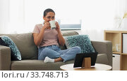 woman with tablet pc drinking coffee at home. Стоковое видео, видеограф Syda Productions / Фотобанк Лори
