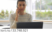 Купить «young woman calling on smartphone at home office», видеоролик № 33748921, снято 11 апреля 2020 г. (c) Syda Productions / Фотобанк Лори