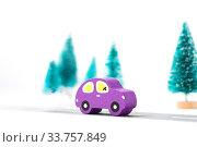 Купить «Wooden car on paper road against fir-trees on white background. Traffic on country road», фото № 33757849, снято 13 мая 2020 г. (c) Papoyan Irina / Фотобанк Лори