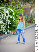 Купить «Little cool girl in jeans stands on the pavement and holds a skate in her hands», фото № 33758437, снято 12 мая 2020 г. (c) Екатерина Кузнецова / Фотобанк Лори