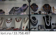 Купить «Close up of natural stone bead necklaces in jewelry shop», видеоролик № 33758497, снято 31 октября 2019 г. (c) Яков Филимонов / Фотобанк Лори