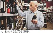Купить «Attentive pensioner chooses red wine in a liquor store», видеоролик № 33758569, снято 24 мая 2020 г. (c) Яков Филимонов / Фотобанк Лори