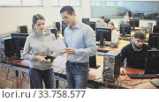 Купить «Female teacher helping young male student in computer class in university», видеоролик № 33758577, снято 1 июля 2020 г. (c) Яков Филимонов / Фотобанк Лори