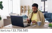 ill man with medicines having video call on laptop. Стоковое видео, видеограф Syda Productions / Фотобанк Лори