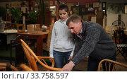Купить «Portrait of young man and woman looking for garden chairs at showroom», видеоролик № 33758597, снято 17 марта 2020 г. (c) Яков Филимонов / Фотобанк Лори