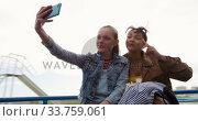 Купить «Front view of a Caucasian and a mixed race girl taking selfie on a merry-go-round», видеоролик № 33759061, снято 9 августа 2019 г. (c) Wavebreak Media / Фотобанк Лори