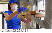 delivery girl in mask giving pizza boxes to woman. Стоковое видео, видеограф Syda Productions / Фотобанк Лори
