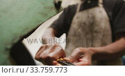 Купить «African American male factory worker at a factory standing at a workbench and working on a metal», видеоролик № 33759773, снято 23 ноября 2019 г. (c) Wavebreak Media / Фотобанк Лори