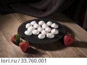 Купить «Portioned meringues on a black plate with whole strawberries on a rustic wooden table», фото № 33760001, снято 8 мая 2020 г. (c) Ирина Кожемякина / Фотобанк Лори
