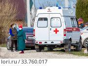 Молодая и пожилая женщины в медицинских масках около машины скорой помощи. Госпитализация во время коронавируса. (2020 год). Редакционное фото, фотограф Светлана Голинкевич / Фотобанк Лори
