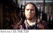 Купить «Man woodcutter with ax standing in front of the camera and looking in the camera», видеоролик № 33768729, снято 2 июня 2020 г. (c) Константин Шишкин / Фотобанк Лори