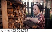 Купить «Young man woodcutter putting logs in the stand», видеоролик № 33768785, снято 2 июня 2020 г. (c) Константин Шишкин / Фотобанк Лори