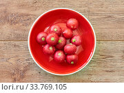 Bunch of raw pink radishes on a red plate on a wooden tabletop. Стоковое фото, фотограф Евгений Харитонов / Фотобанк Лори