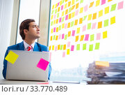 Купить «Young handsome employee with many conflicting priorities», фото № 33770489, снято 15 августа 2018 г. (c) Elnur / Фотобанк Лори