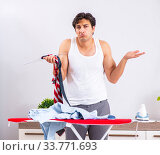 Купить «Young man ironing in the bedroom», фото № 33771693, снято 27 июня 2018 г. (c) Elnur / Фотобанк Лори