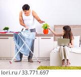 Купить «Man ironing, his lazy wife sitting», фото № 33771697, снято 27 июня 2018 г. (c) Elnur / Фотобанк Лори