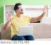 Купить «Young man with virtual reality goggles», фото № 33772161, снято 8 мая 2018 г. (c) Elnur / Фотобанк Лори