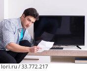 Купить «Man trying to fix broken tv», фото № 33772217, снято 9 марта 2018 г. (c) Elnur / Фотобанк Лори