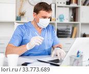 Купить «Man doctor in face mask working at laptop», фото № 33773689, снято 13 июля 2020 г. (c) Яков Филимонов / Фотобанк Лори
