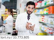 Male specialist is attentively stocktaking medicines with notebook near shelves in pharmacy. Стоковое фото, фотограф Яков Филимонов / Фотобанк Лори