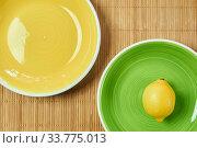 Lemon on a green plate next to a yellow empty plate on a cane tablecloth. Стоковое фото, фотограф Евгений Харитонов / Фотобанк Лори