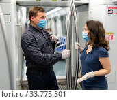 Man and woman in protective medical masks talking with woman while traveling by subway. Стоковое фото, фотограф Яков Филимонов / Фотобанк Лори