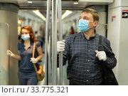 Man in medical mask riding in subway car. Стоковое фото, фотограф Яков Филимонов / Фотобанк Лори
