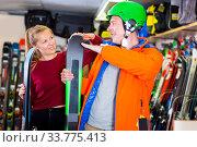Купить «Saleswoman is helping man in ski equipment», фото № 33775413, снято 31 июля 2017 г. (c) Яков Филимонов / Фотобанк Лори