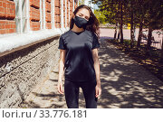Young woman in a black t-shirt and a protective face mask stands on the street. Стоковое фото, фотограф Женя Канашкин / Фотобанк Лори