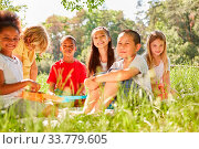 Купить «Multikulturelle Kinder Gruppe beim Picknick auf einer Wiese im Sommer», фото № 33779605, снято 25 мая 2020 г. (c) age Fotostock / Фотобанк Лори
